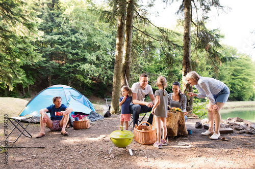Fotobehang Kamperen Beautiful family camping in forest, eating together.
