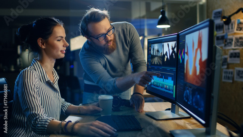 Female Video and Sound Editor Works With Her Male Colleague on a Project on Her Personal Computer with Two Displays Canvas Print