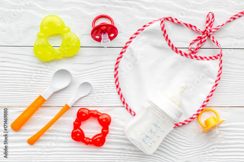 bottle with breastmilk and infant formula powdered healthy food, toys and bib on Fototapet