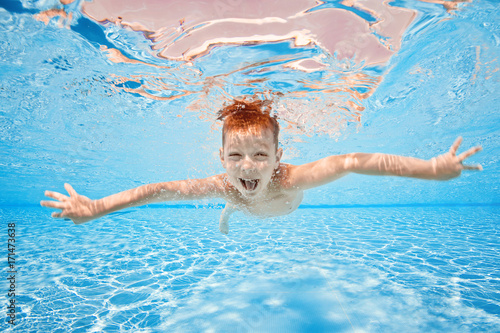 Fotografie, Obraz  Happy young boy swim and dive underwater, kid breast stroke with fun in pool