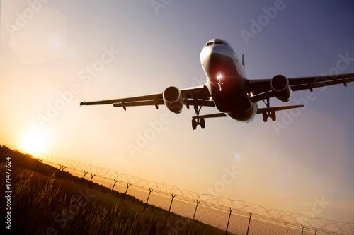 Foto  starting airplane in front of a the evening sun