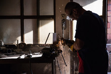 A Man In A Workshop Using An I...