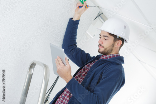 Valokuva  male electrician with screwdriver repairing fire sensor