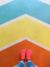 Person Wearing Running Shoes Looking Down A Colorful Arrow Shapes.