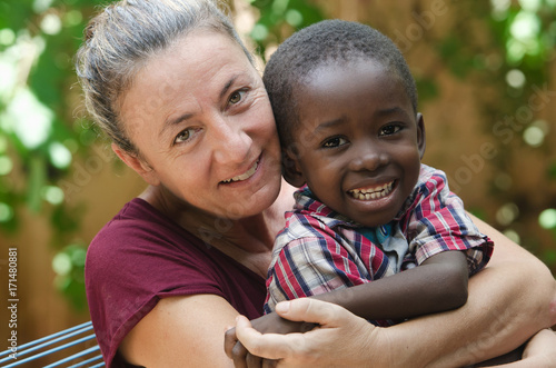 Photo Adoption symbol - Woman adopts a little African boy