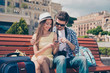 Modern youth is travelling, using technology devices, internet, enjoying. Teens sit outdoors with camera and pda, in cap and spectacles