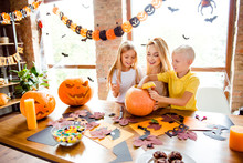 Blonde Boy Puts Candle Inside The Jackolantern, Mother And Sister Are Curious, Laughing, Peeking Inside It. Craft Materials, Yellow Candles, Treats, Autumn Leaves On Table, Garlands, Bats On Windows
