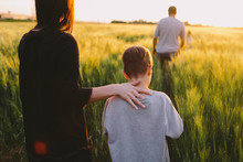 Mother And Son Walking Away Through The Field