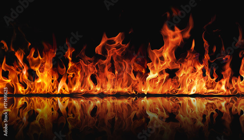 The texture of fire on a black background is reflected in a glossy table Canvas Print