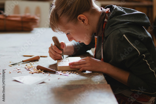 Woman carpenter carves a wooden stamp