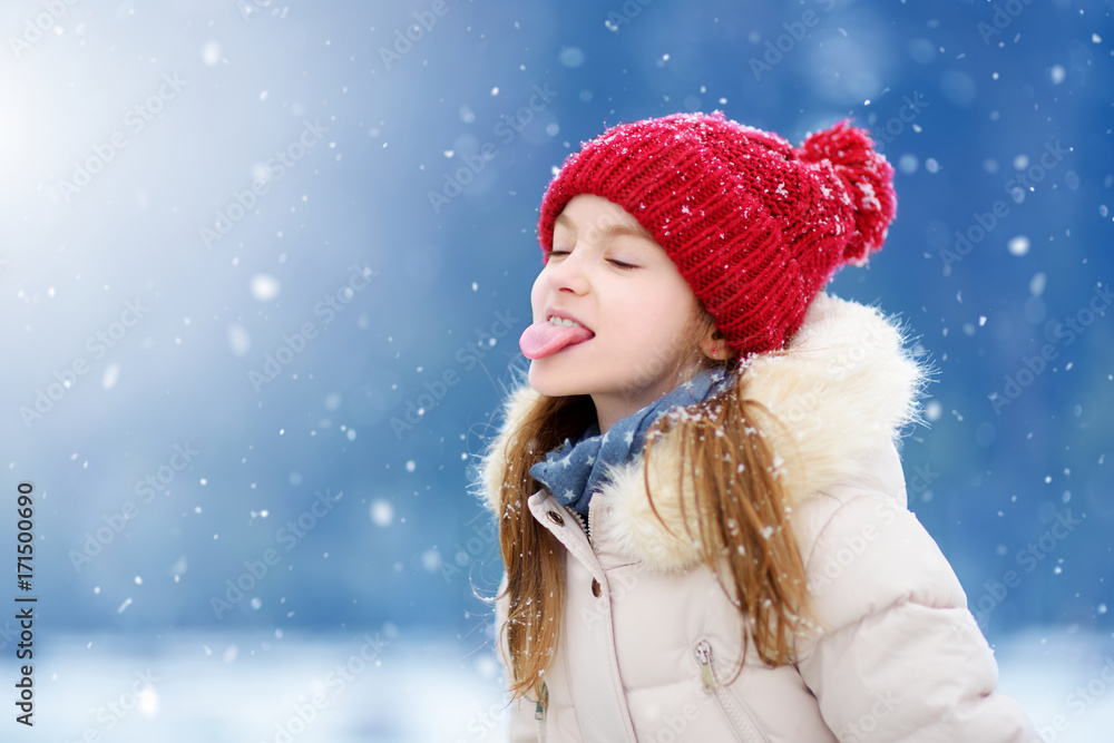 Fototapeta Adorable little girl catching snowflakes with her tongue in beautiful winter park. Cute child playing in a snow.