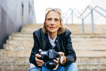 Senior Woman Holding Her Camera Sitting On Stairs.
