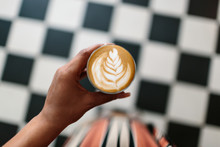 A Woman Holding A Cortado And Looking Down At A Checkered Floor.
