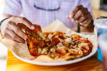 Close-up Of Man Eating A Whole Meat Supreme Pizza