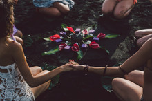 Women On The Beach Join Hands Around The Flower Mandala