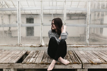 Young Woman Sitting Cross Legged In Front Of Old Abandoned Greenhouse