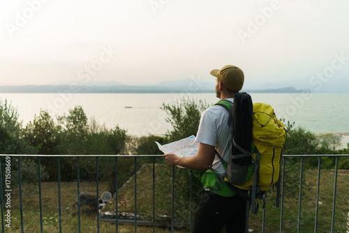 Backpacker with map on nature