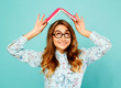 Leinwanddruck Bild Beautiful young student holding book on her head and wearing glasses over blue background
