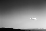 Minimalist view of an almost empty sky with a small white cloud, over some distant mountains and hills - 171537064