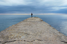 A Lone Fisherman On The Pier