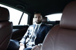 Successful businessman sitting in the back seat of a car