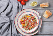 Salad with quinoa, tomatoes and onion served on grey wooden background