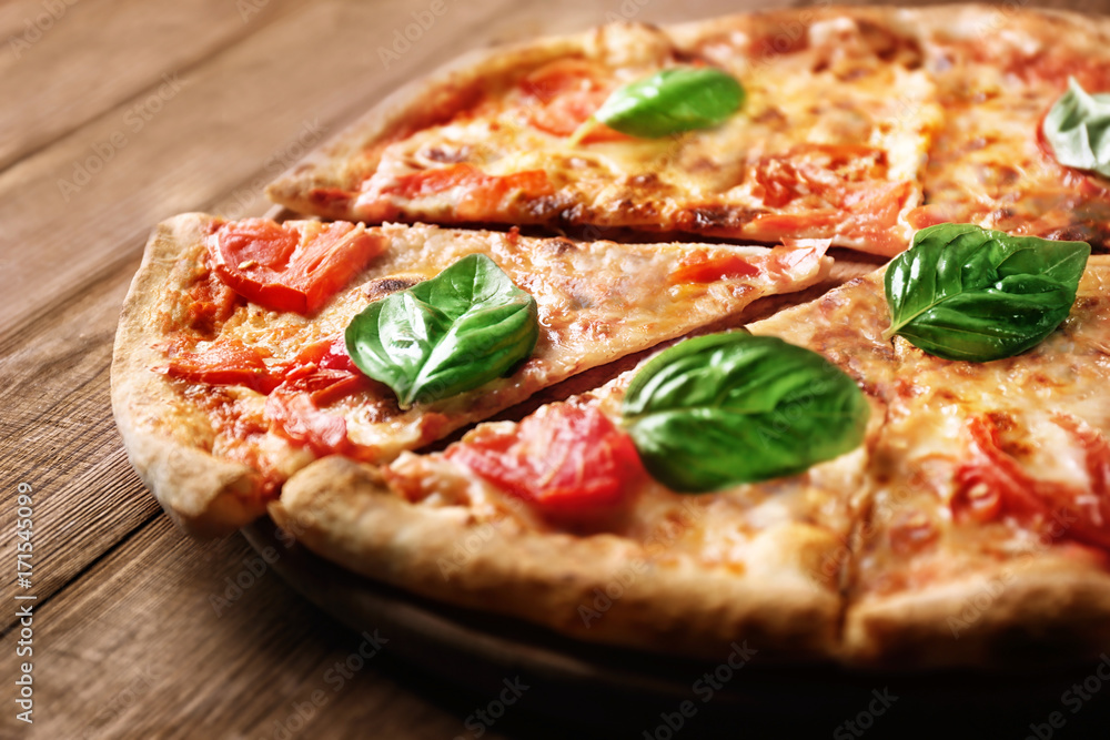 Delicious pizza with tomatoes and fresh basil on wooden background