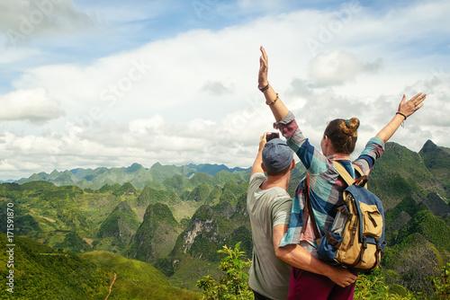 Plakat para turystów, co selfie na tle gór krasowych.