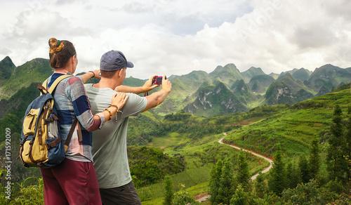 Plakat Para turysta robi fotografia krasowym górom.