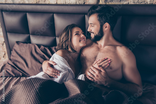 Fototapeta Close up cropped photo of stunning young sexy brunette embracing her lover in bed, he is bearded handsome brunet, smiles, looks at her. Lady is gorgeous and hot obraz