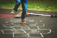 Little Boy Playing Hopscotch O...