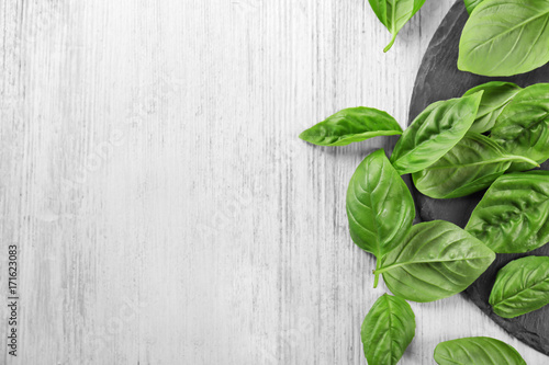 Papiers peints Herbe, epice 2 Green fresh organic basil leaves on wooden background