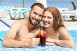 Happy couple drinking cocktail in swimming pool