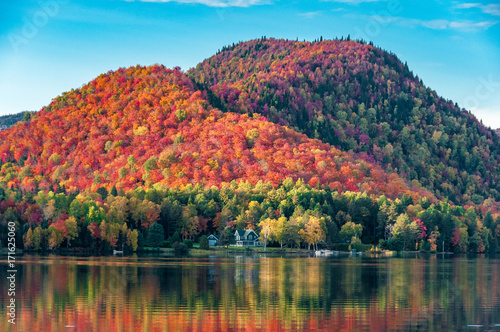 Canvas Print The hills covered with red maple forests behind a wooden house on the shore of a lake  in Quebec, on a beautiful autumn evening