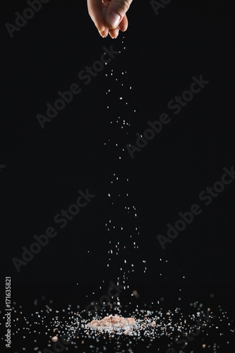 Scattered sea salt against black background