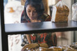 Young asian woman buying bread in a bakery