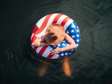 Girl Wearing Hat In American Flag Float In Lake