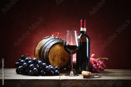 Fotografía  Red wine glass with bunches of grapes, bottle and small barrel