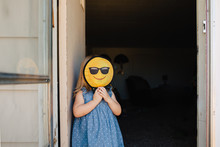 Toddler Girl With A Happy Smiley Emoticon Face In Front Of Her Face.