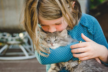 Young Child Holding And Kissing A Kitten On The Head