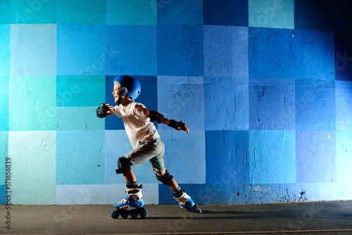 Cute little boy on roller skates running against the blue graffiti wall