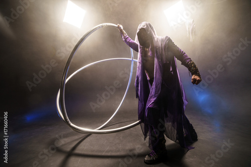 Photo  Fairy-tale character assassin in a purple cloak with a hood with two large cross