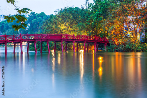 hanoi Red Bridge at night. The wooden red-painted bridge over the Hoan Kiem Lake connects the shore and the Jade Island on which Ngoc Son Temple stands.