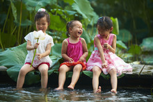 Three Little Girls Sitting By The Pond Playing Water