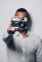 Man Holding Old Camera While S...
