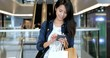 Asian Woman holding shopping bags and using smart phone