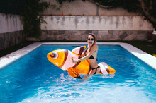 Funny Young Woman On Top Of A Mattress Fish In The Pool