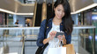 Woman go shopping and carry shopping bags and cellphone