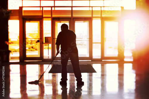 Fotomural Janitor mopping an office floor, shallow focus, tilt shift image