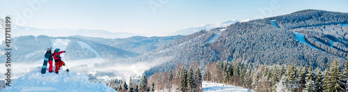 obraz dibond Extra wide panorama of the Carpathians mountains landscape, forests in a white haze, ski slopes, winter ski resort Bukovel. Two snowboarders enjoying, resting on top of the mountain on a sunny day